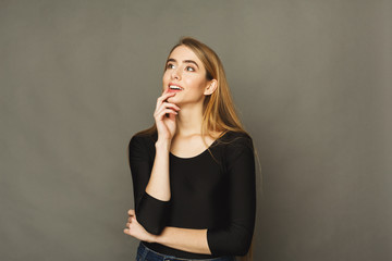 Happy woman thinking on brown background