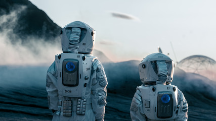 Shot of Two Astronauts Confidently Walking on Alien Rocky Planet that is Covered with Gas and Smoke. Humans Overcoming Difficulties. Scientific Progress.