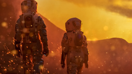 Two Astronauts Wearing Space Suits Exploring High Temperature Venus/ Red Planet During Fire Storm/ Sunset. Space Travel and Solar System Colonization Concept.