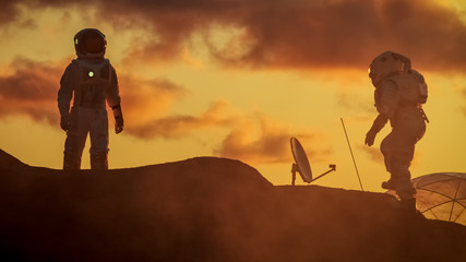 Two Silhouettes of the Astronauts Explore Red Rocky Alien Planet. In the Background Sunset with Base/ Research Station.