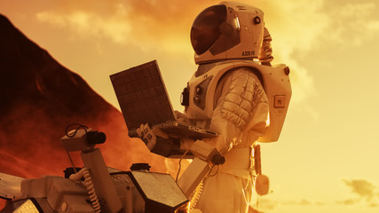 Astronaut in the Space Suit Works on Laptop, Adjusting Rover on a New Alien Red Planet, Presumably Mars. Day Light High-Tech Space Exploration, Mission, Discovering and Colonizing Habitable Planets.