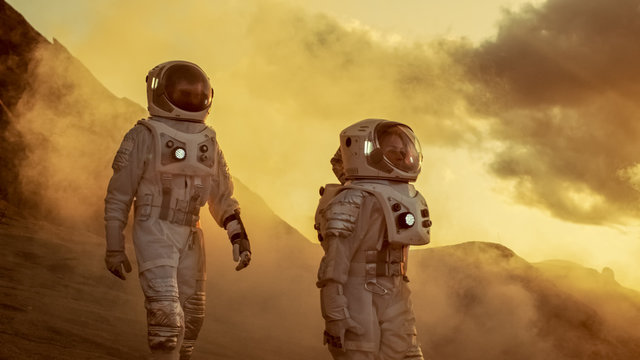 Two Astronauts in Space Suits Confidently Walking on Mars, Exploration Expedition on the Planet's Surface. Red Planet Covered in Rocks, Gas and Smoke. Humans Overcoming Difficulties.