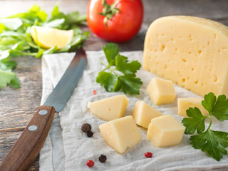 Piece of cheese with parsley, tomatoes on a linen towel Rustic wooden background