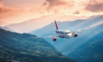 Aircraft is flying over green hills against mountains with yellow sunbeams at sunset. Landscape with passenger airplane, colorful sky, village. Passenger aircraft. Business travel. Commercial plane Fototapete