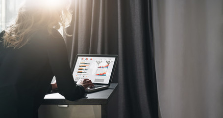 Rear view. Young businesswoman is sitting at table, working on laptop with graphs, charts, diagrams, schedules on screen