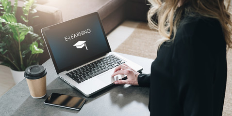 Rear view. Young woman is working on laptop with inscription on screen e-learning and image of square academic cap. Wall mural