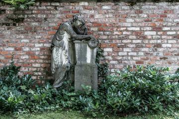 Altes Grab an einer Friedhofsmauer