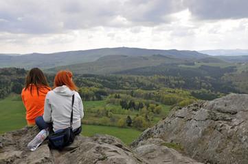 """zwei frauen sitzen auf dem felsen """"milseburg"""" und schauen  über die bewaldete rhönlandschaft zur wasserkuppe"""