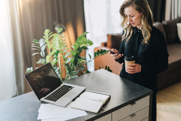 Young smiling businesswoman in black blouse is standing indoor, working on computer while using smartphone.