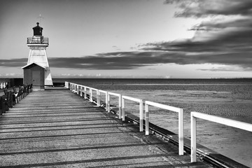 Old fashioned lighthouse on the end of a pier, vast water and cloud beyond. Black and white art