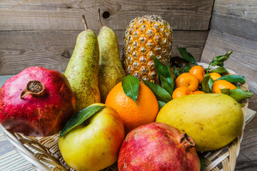 Fresh fruit in a basket on wooden table.;