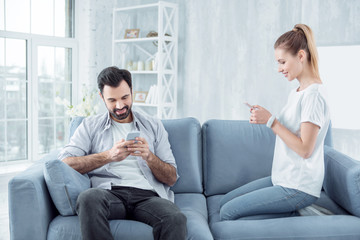 Online chat. Charming girl keeping smile on her face and looking at her gadget while sitting in semi position