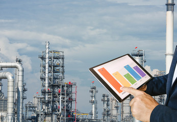 businessman fingers touching chart tablet against oil refinery in petrochemical Aerial view oil refinery night during twilight,Industrial zone,Energy power station