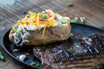 loaded baked potato with steak on cast iron pan