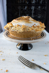 lemon meringue pie on white table with fork and crumbs