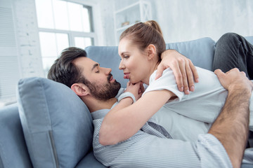 Lets joke. Joyful female person lying on her boyfriend and showing tongue while having rest