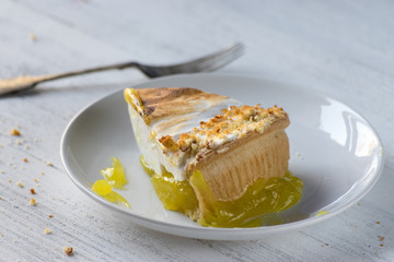 cut lemon meringue pie with thick slice on white plate on white table with fork and crumbs