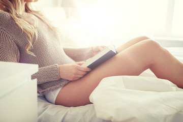 Fototapete - close up of woman reading book in bed at home