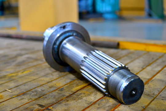 The new splined shaft after machining on the lathe and CNC milling machine lies on a wooden rack in the shop.