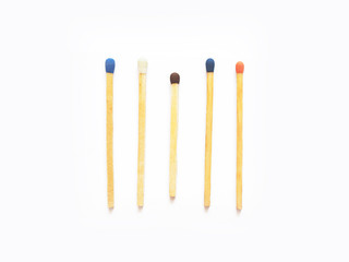 Wooden matches with heads of different colors. Five match sticks isolated on white background, close-up. Berthollet salt, sulfur