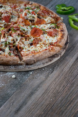 sliced pepperoni pizza with green peppers on dark gray wood table