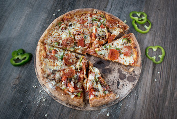 sliced pepperoni pizza with green peppers on dark gray wood table top view