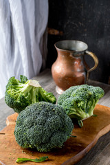 fresh broccoli heads on cutting boards in farmhouse setting with copper