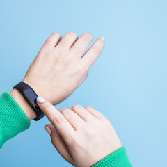 The woman presses her fitness bracelet on her arm. Hands in a sporty bright green jacket on a blue background. Healthy lifestyle and fitness concept