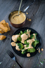 steamed broccoli florets on plate covered in cheese sauce in rustic farmhouse setting top view
