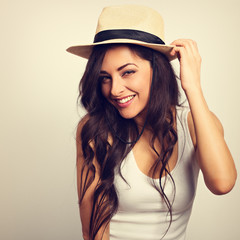 Beautiful long hair laBeautiful long hair laughing woman in white top and straw hat looking happy. Toned vintage portrait