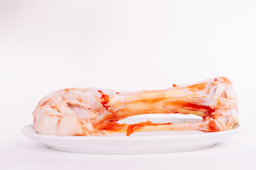 in a white plate is a damp chicken bone with blood and meat