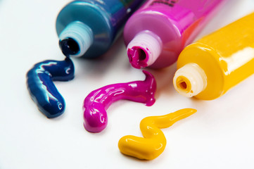 Tubes with acrylic blue, yellow and pink paint on white background