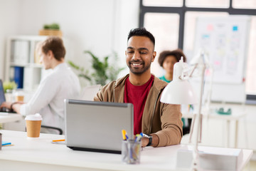business and creative people concept - happy smiling young indian man with laptop computer working at office
