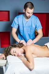 Massage therapist massaging back beautiful brunette woman in spa