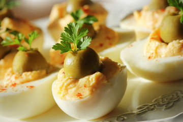 Spicy deviled eggs garnished with green olives and parsley
