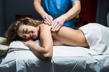 Young woman receiving a back massage in spa center. Female patient is receiving treatment by professional therapist.
