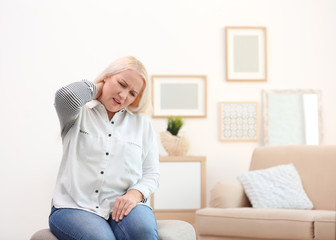 Mature woman suffering from neck pain at home