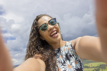 Young girl take selfie from hands with phone on summer mountain top. Rural life concept.