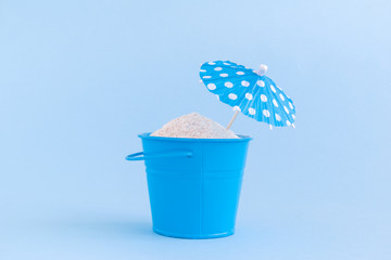 Can with sand and paper cocktail parasol isolated on blue background. Summertime vacation minimalistic still life concept.