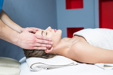 massage of face for young woman in spa salon