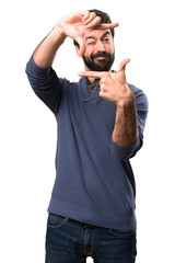 Handsome brunette man with beard focusing with his fingers on white background