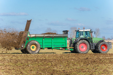 Tractor with manure spreader on the field - 1298