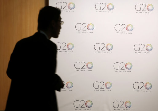 A man stands next to a board with the G20 Meeting of Finance Ministers logo in Buenos Aires