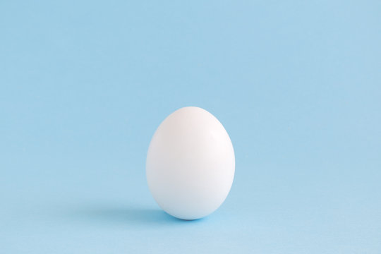 White egg isolated on pale blue background.