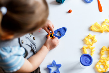 Close up picture of a child playing with  color play dough and cutters. Having fun with colorful modeling clay. Creative kids molding at home. Children play with plasticine or dough.