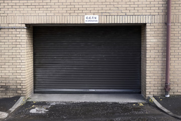 CCTV in operation sign above garage door shutter