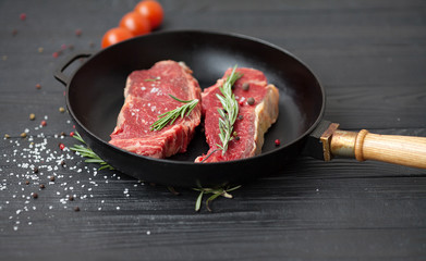 raw steak on cast iron frying pan