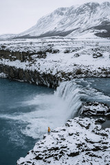 Male in yellow jacket standing on the edge of a waterfall in Iceland with mountain in the background during winter