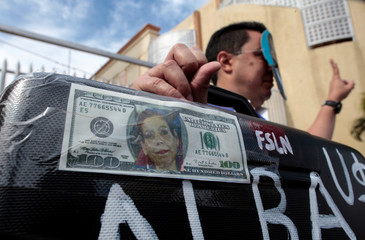 A man holds a suitcase displaying U.S. dollar bill with an image of Vice President and First Lady Rosario Murillo, during a protest outside the National Assembly in Managua