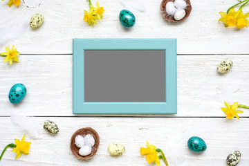 blank photo card in frame made of quail eggs, spring flowers and feathers on white wooden background